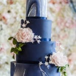 Wedding Cake and a flower wall backdrop