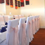 Baby pink lace sashes teamed with navy blue table runners make fabulous friends-FabulousFunctionsUK