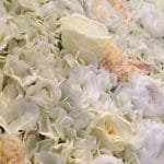 Floralie-Silk flower wall in tones of cream and white with hints of greenery and coral
