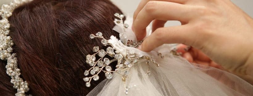 Bride having veil pinned to her hair - wedding traditions from around the world