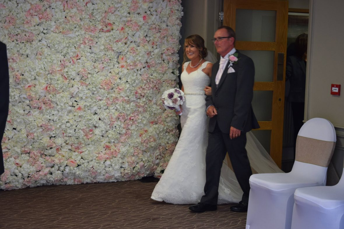 The flower wall was used to create a stunning entrance for the bride and her father.  Accessory Hire from Fabulous Function UK