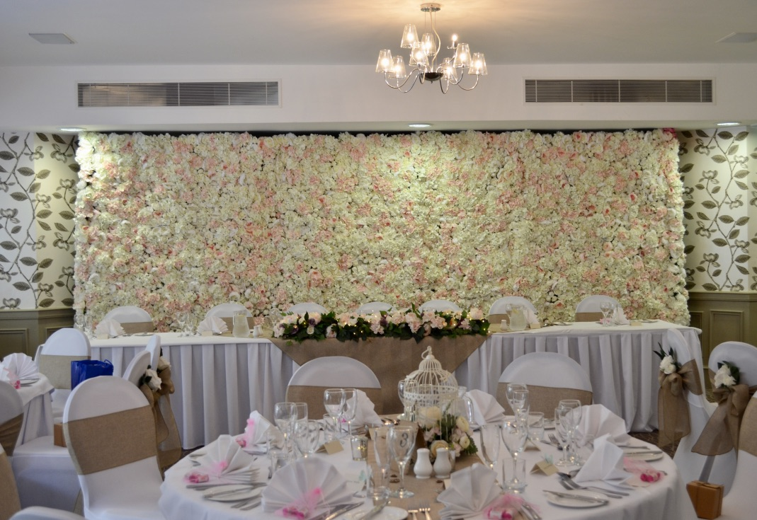 Rustic themed wedding decor with flower wall and bird cage centrepieces