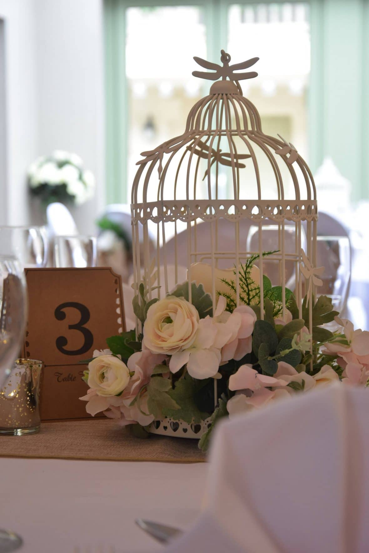 Centrepiece of a birdcage filled with flowers perfect for a rustic themed venue decor