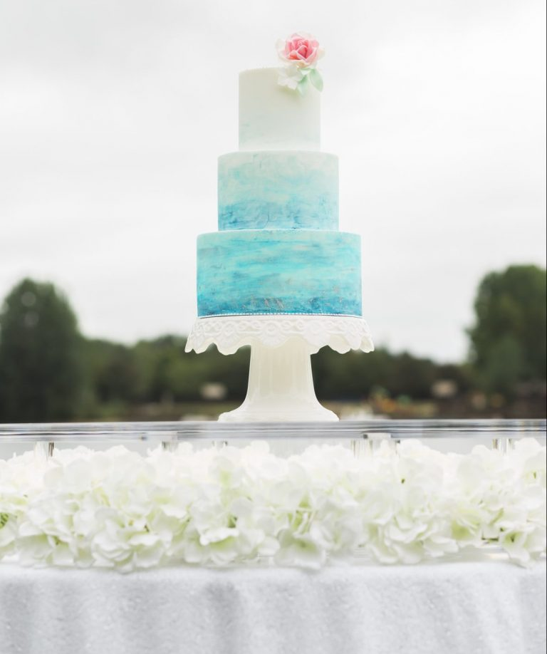 Water colour decorated wedding cake on floating cake table