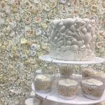 Flower wall backdrop to Sea shells decorate the top tier- Fabulous Functions UK
