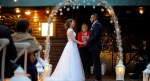Sam and Kat say their I Do's under an arch with falling snowflakes