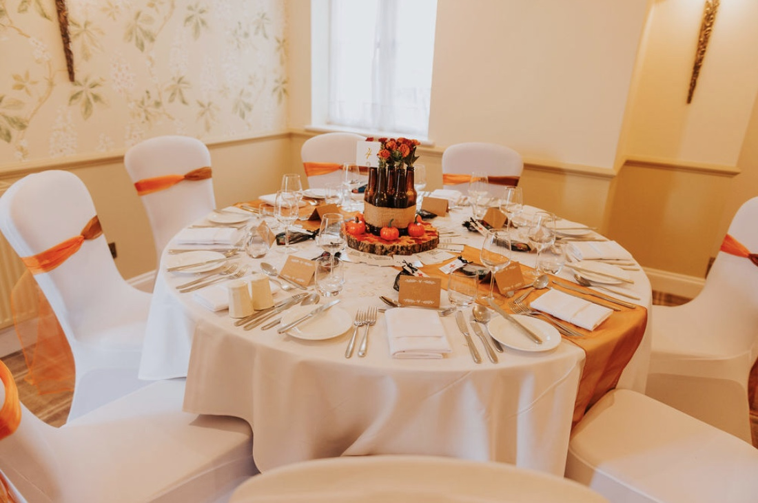 Autumn themed table decor using glorious rich rusts and golds to create a warm, welcoming wedding decor.