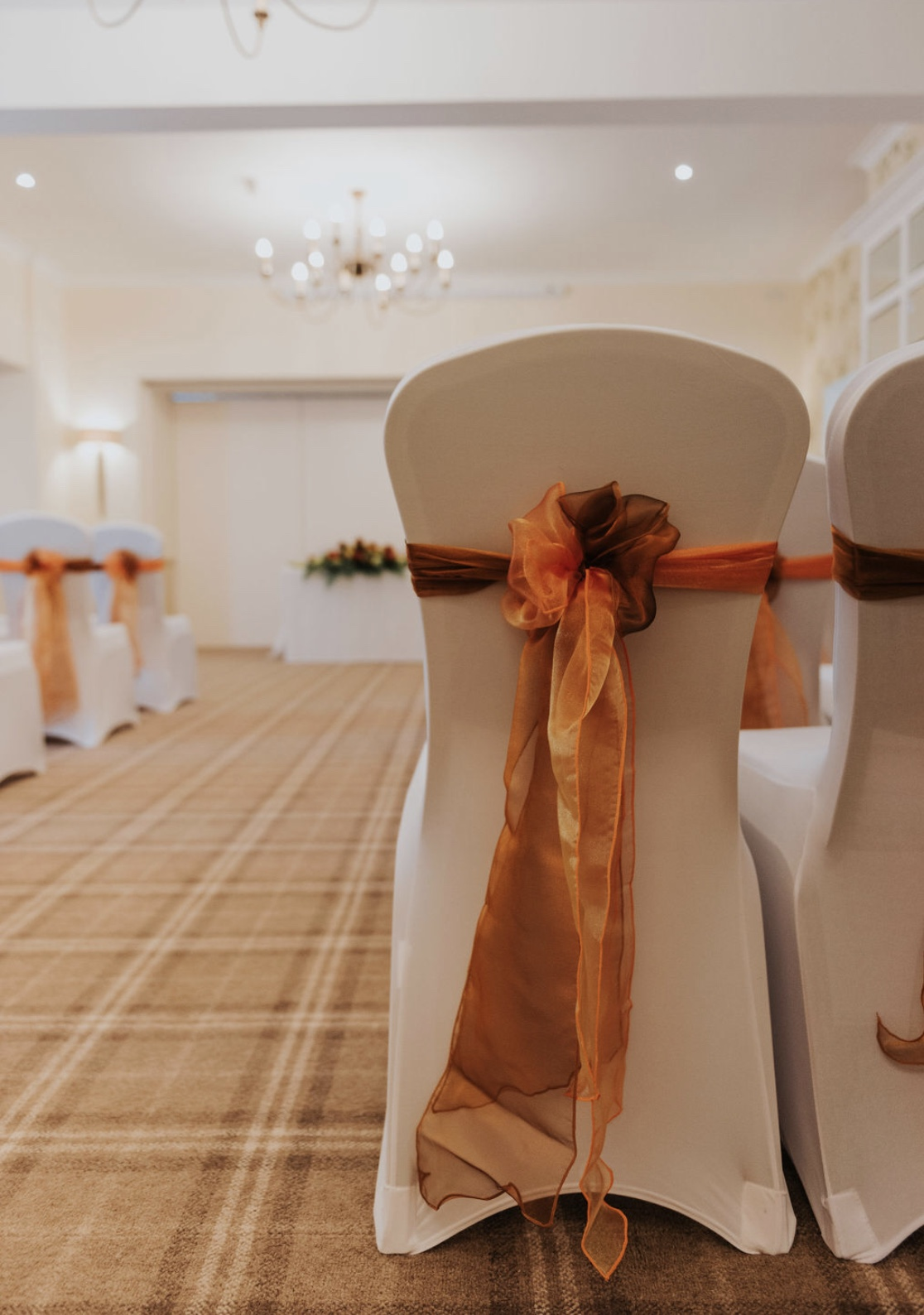 Shimmering organza sashes in golds and rusts to decorate the ceremony venue