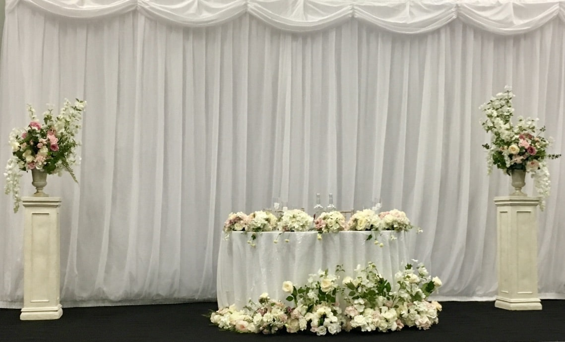 This wedding staging is created by Fabulous Functions UK and  included a sweetheart table decorated with an abundance of flowers. There were flowers on the table, flowers surrounding the table and two floral arrangements on pedestals either side if the sweetheart table