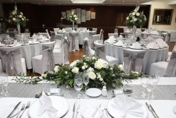 A Silver and grey themed wedding decor featuring silver grey table cloth, silver satin and silver lace sashes white charger plates with diamante rims. Blush pinlk flower wall and white florals with greenery-Fabulous Function UK