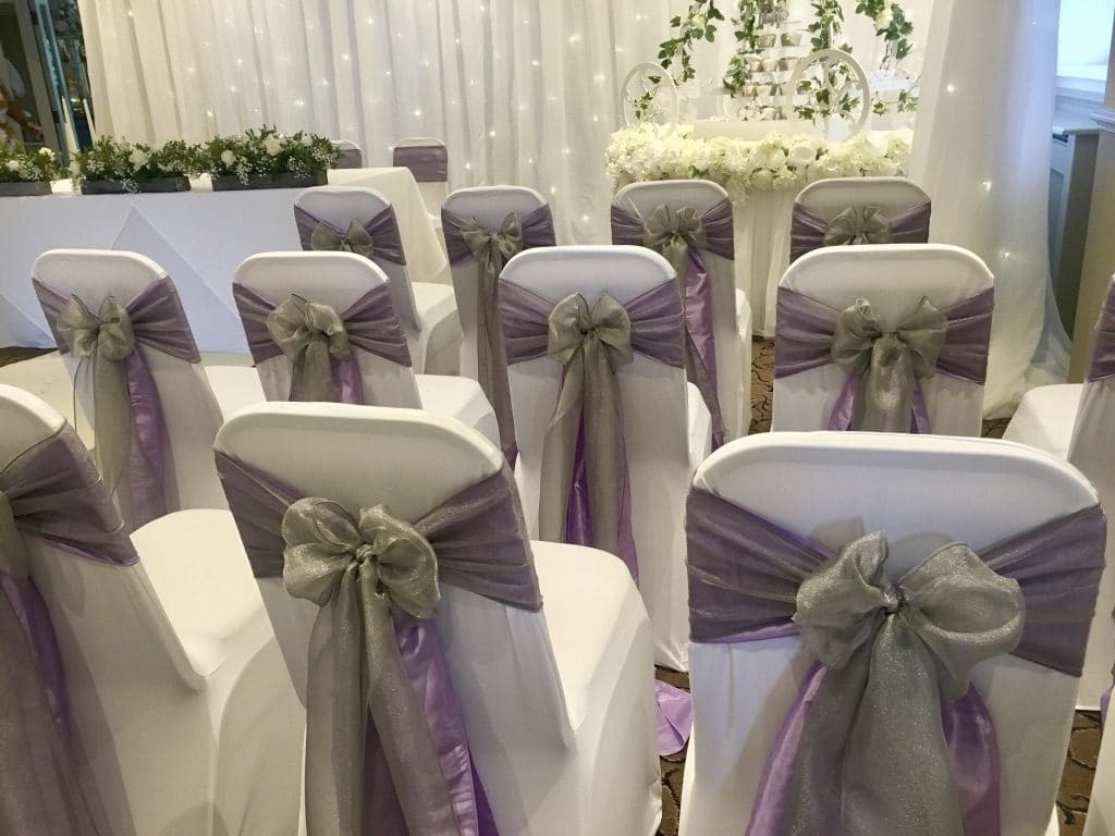 Lilac taffeta sashes with an overlay of shimmering platinum  organza sashes for this gorgeous venue decor-Fabulous Functions UK