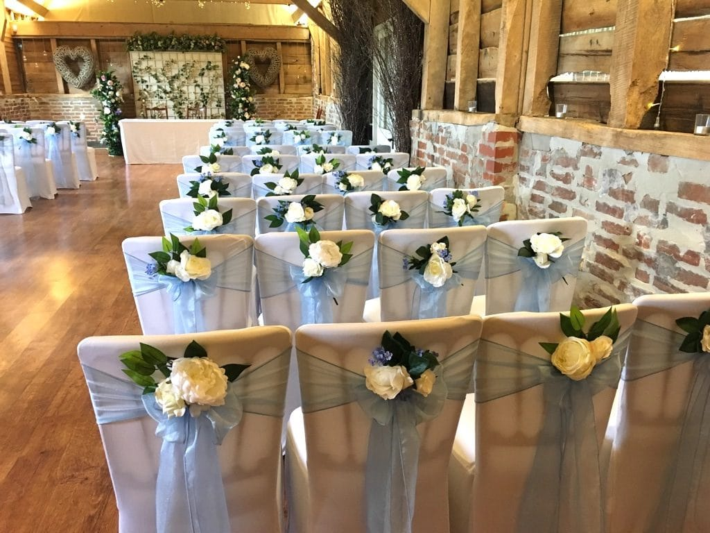 Wedding chairs are decorated with  gorgeous sparkling organza sashes and decorated with a small posy tucked into the back of the bows