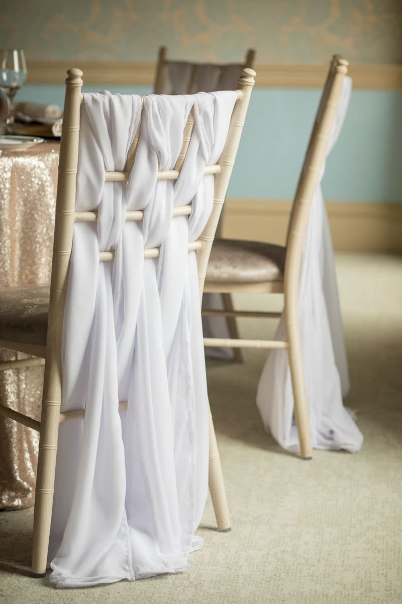 Chiffon vertical drapes are used in a sophisticated weaved design to dec orated these chiavri chairs design created by Fabulous Functions UK