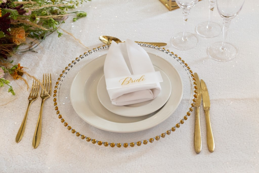 Place setting of gold beaded edged glass charger plate with acrylic guest name plates - guest names written in gold coloured font and displayed on a  white folded  napkin.
