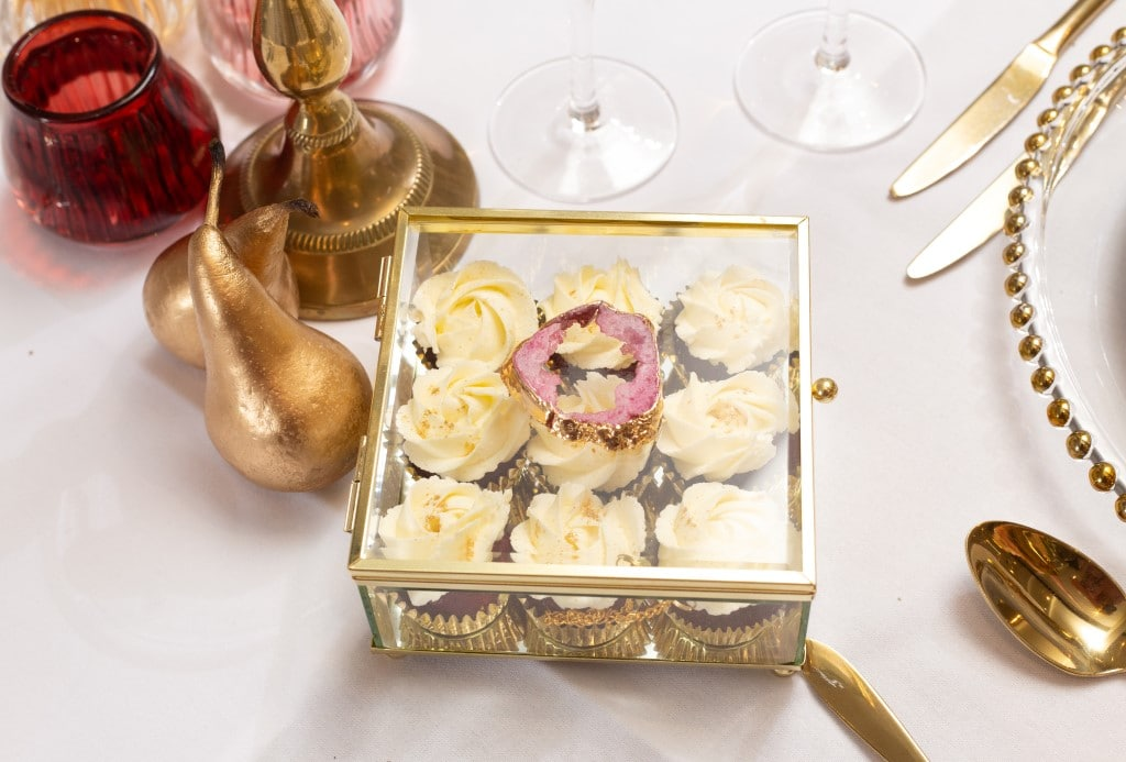 cupcakes nibbles for the guests displayed in a glass box with agate slice decor on the lid