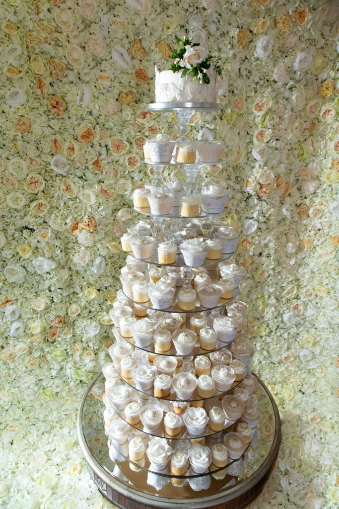 Flower wall with crystal seven tier cake tower in front of it. Photoshoot at the Bear Hotel in Hungerford