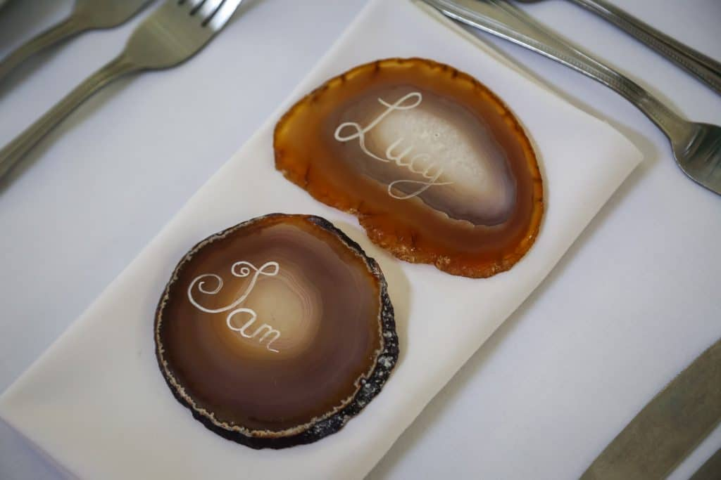 Agate slice in natural tones serve as guest place names.  The colour of the agate slices complement the rose gold theme of the chair decorations. The perfect wedding favour and memento for your guests. Available from Fabulous Functions UK
