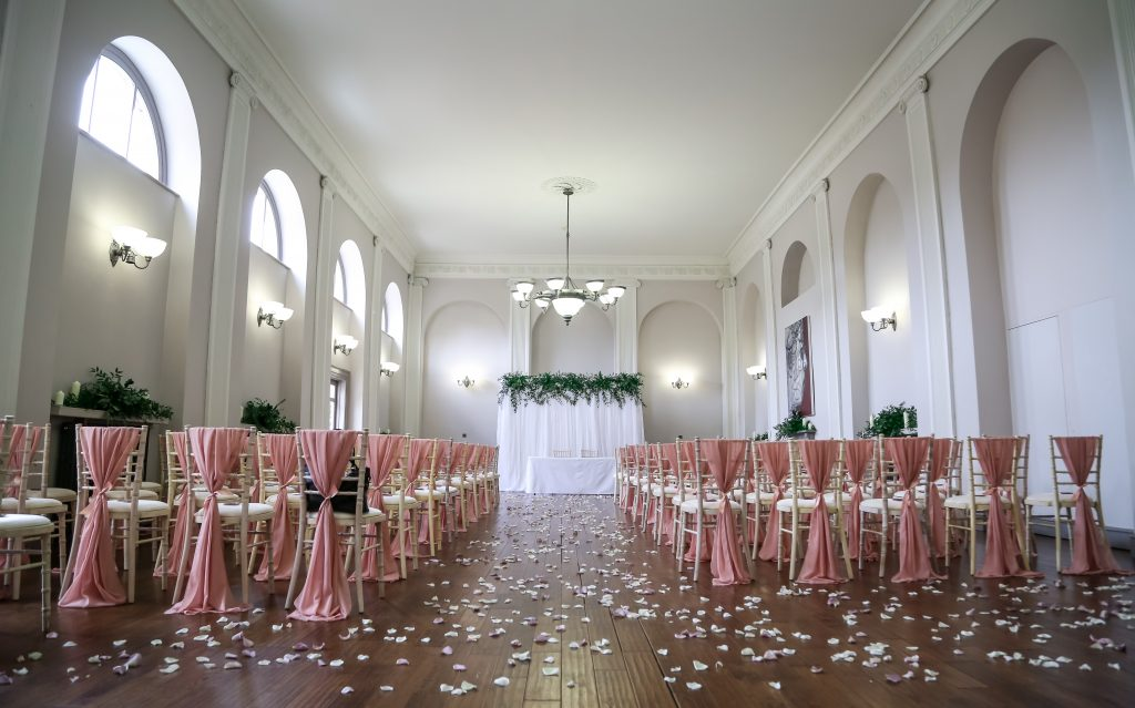 Rose gold chiffon vertical drops serve to decorate the chiavari chairs in the Assembly Rooms of the Kings Head Hotel in Cirencester. The backdrop was created with a white voile draped panel and green foliage for the top border decoration. Styling by Fabulous Functions UK