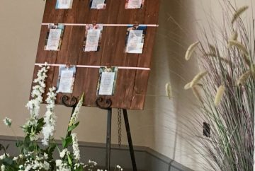 Fabulous Functions UK created the table plan A reclaimed wooden board was the base for the table plan. Rose gold ribbons were used to attach the guest tables. The white and green floral decor continued the floral theme from the wedding breakfast decoration.