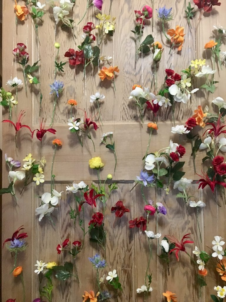 Are Cheap Wedding Backdrops Cheap at all? -Floral curtain created with small florals in a rainbow of colours. A beautiful backdrop but time consuming to make and transport to the venue for installations.