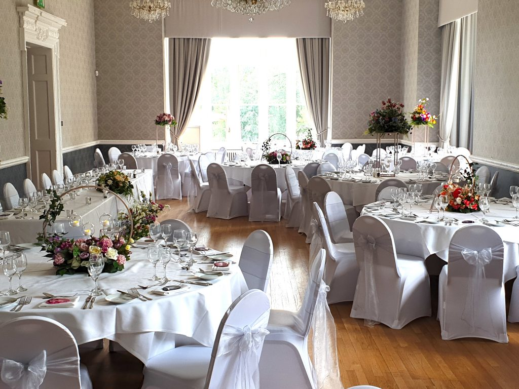 Venue styling using a combination of tall and low centrepieces -Fabulous Functions UK