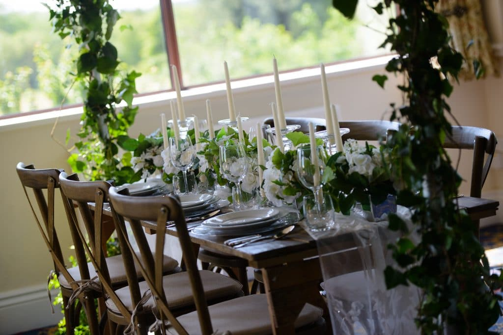 Rustic wedding breakfast setting for an intimate wedding scene  - bare wooden table dressed with a chiffon runner and white flowers and greenery. With an overhead arch of foliage.
