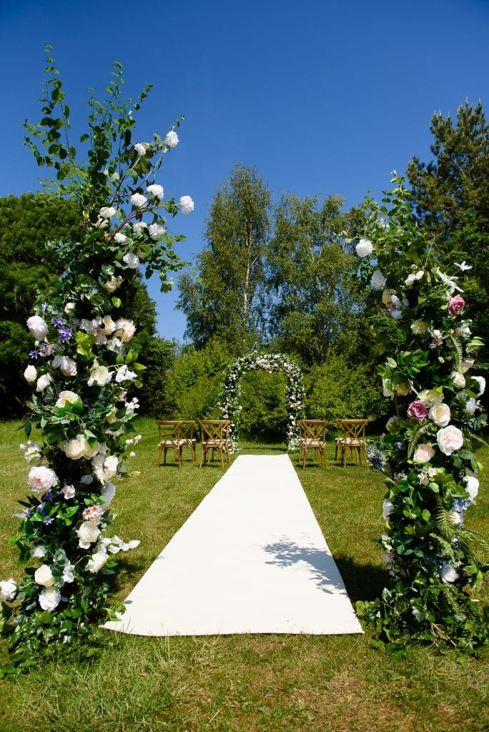 An Intimate Wedding Setting - floral and greenery archways at either end of a cream aisle carpet in a meadow setting at Wrag Barn golf club Nr Highworth, Swindon