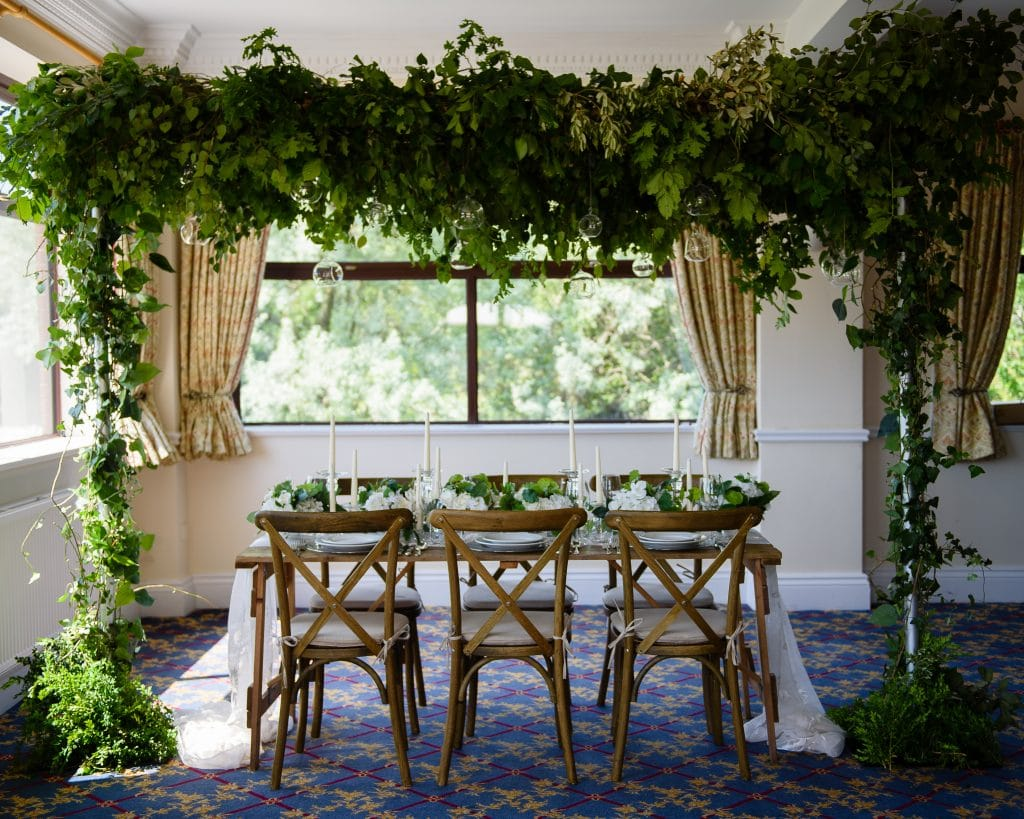 Table and chairs under an archway of green folliage