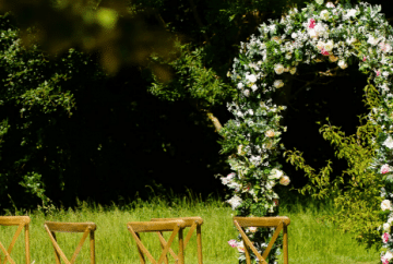 Floral arch backdrop for an outdoor wedding ceremony - Fabulous Functions UK
