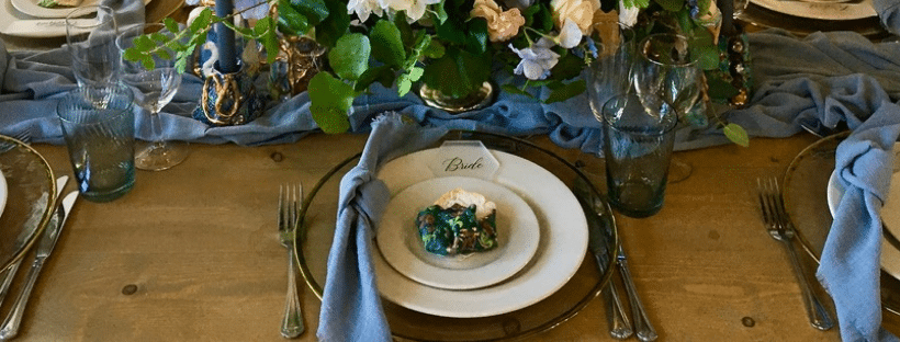 Charger plates are used to dress a table for a wedding or special event. These gold rimmed charger plates are a perfect complement to the wooden table set in a banquet style for the guests. Created by Wedding Designer Fabulous Functions UK