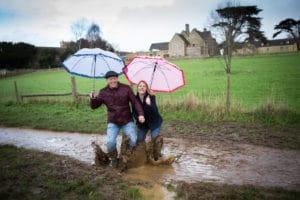 Couple under umbrellas splashing in mud
