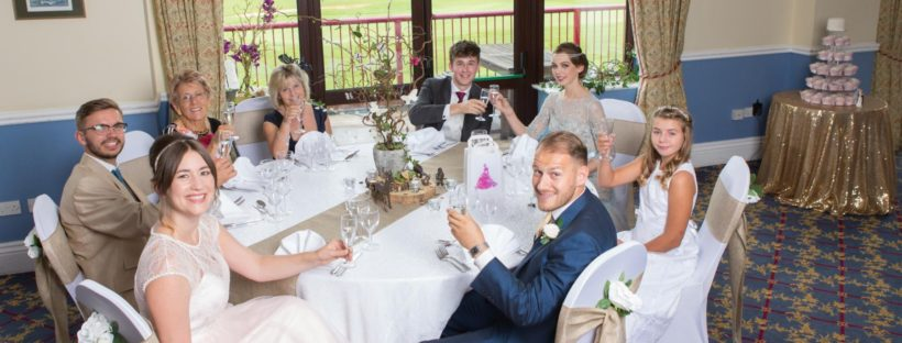 Five Champagne Alternatives for Wedding Toasts - wedding party around a table proposing a toast.