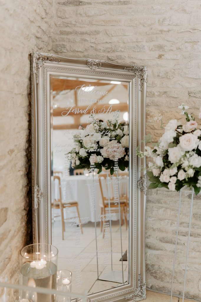 Mirrored Table Plan-  Using a large mirror to create a statement decor in your venue. The guest names were printed in white vinyl  and applied to this beautiful mirror. Add floating candles in various size cylinder vases  to complement the scene. Creted by venue stylist Fabulous Functions UK